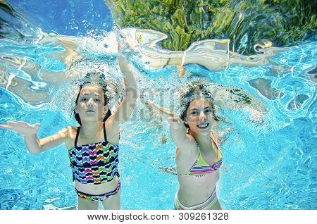 Children Swim Underwater In Swimming Pool, Happy Active Girls Have Fun Under Water, Kids Fitness And