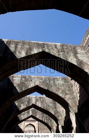 Low Angle View Of Stone Arches Of Hindola Mahal Or Swinging Palace Audience Hall With Sloping Side W