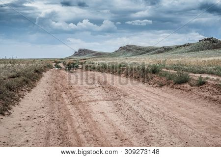 Russia. Astrakhan Region. The Clay Road In The Steppe Among The Hills Against The Backdrop Of A Dram