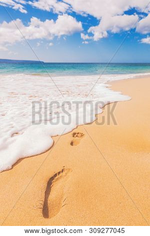 Beach footprint in sand travel vacation vertical background. Holiday footprints disappearing in ocean waves away - footsteps in sand on summer tropical getaway holidays with blue ocean.
