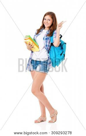 Full length portrait of beautiful student girl with backpack and books. Teen girl showing victory sign, isolated on white background