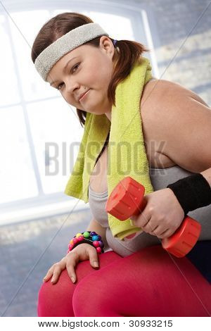Determined fat woman exercising with dumbbells.