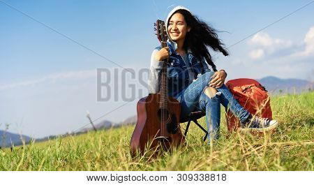 Women Holding A Guitar In Their Hands Sitting In The Grass Field