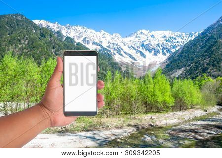 Hand Hold Mobile Phone On A View Of Japan Alps Mountain, Japan