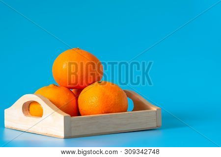 Summer Of Orange Fruit In Wood Box On Blue Background.