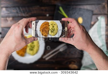 Man Taking Photo Of Fried Chicken Steak Or Schnitzel With Mashed Potatoes On Wood Table