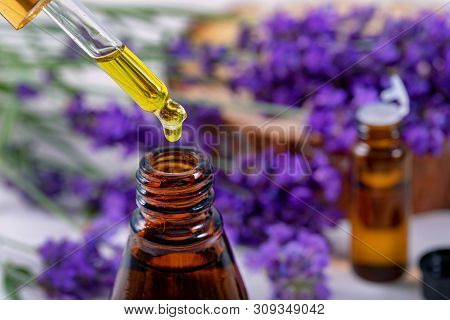 Lavender Essential Oil Drop From Pipette Over The Bottle
