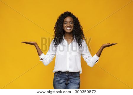Make right choice. Positive african girl comparing variants, making scales with his empty hands, yellow studio background, free space poster