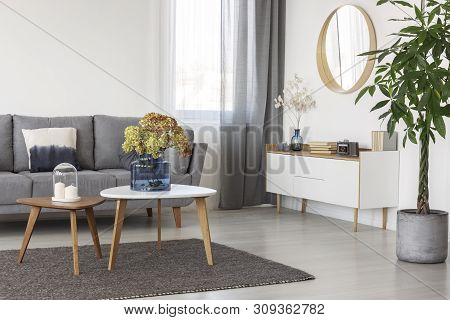 Flowers In Blue Glass Vase On Wooden Coffee Table In Elegant Living Room Interior With White Wooden