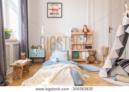 Cozy Kids Bedroom With Blue Bedding And Warm Blanket On The Bed, Real Photo With Mockup Poster On Th