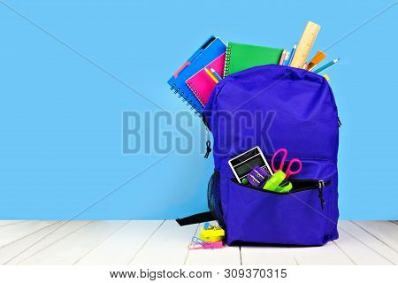 Purple Backpack Full Of School Supplies Against A Blue Background. Back To School Concept. Copy Spac