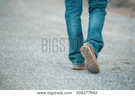 Feet Walking Of Lonely Man,step By Step On The Street.picture Of Journey Person Wearing Jean And Fas