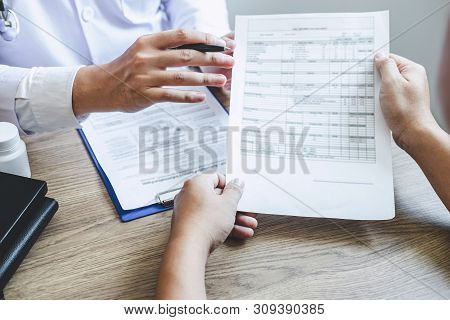 Professional Doctor In White Uniform Gown Coat And Patient Discussing Consults To Treatment Of Sympt
