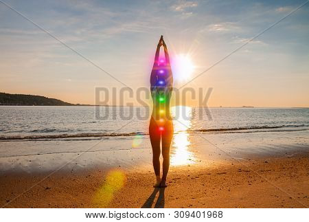 Woman Is Meditating With Glowing Seven Chakras On The Beach. Silhouette Of Woman Is Practicing Yoga