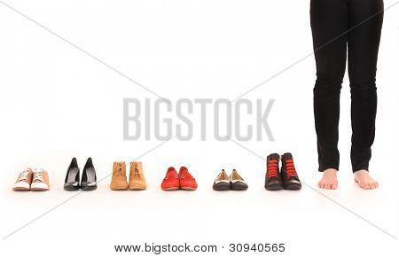 A picture of female legs among six pairs of shoes over white background