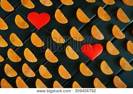 Fruit Marmalade In The Form Of Mandarin Lobules Lies On Dark Painted Boards Next To Two Hearts. The