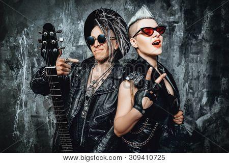 A portrait of two stylish punk men in the street. Modern men fashion, rock musicians.