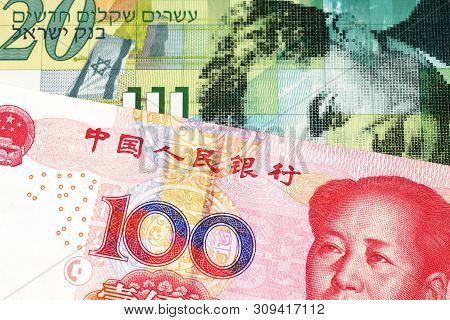 A twenty shekel note from Israel close up in macro with a red, Chinese one hundred yuan renminbi bank note poster