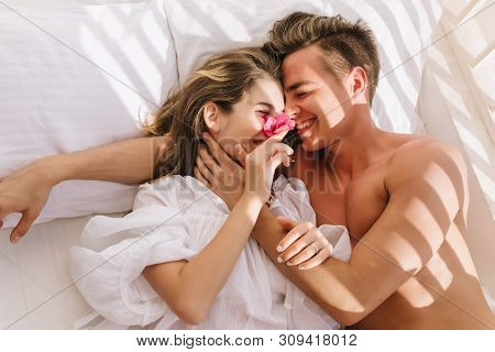 Cheerful Young Couple In Love Lying In White Bed, Enjoying Honeymoon In Sunny Morning. Smiling Hands