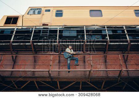 Bluesman With Acoustic Guitar On Railroad Bridge. Cool Guy Plays Guitar Near Running Train. Showy Pe