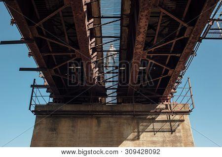 Bluesman With Guitar Case Walks On Railroad Bridge. Silhouette Of Blues Musician On Rusty Railway Br