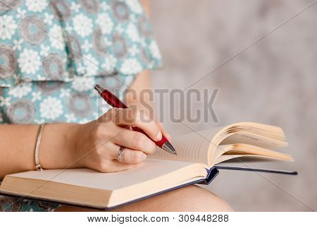 Front View Of Womans Hands Writing Useful Information In Notepad.girls Hand With A Red Pen Writes Th