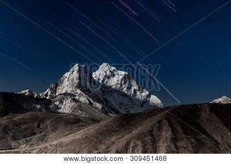 Stars falling above Ama Dablam mountain peak lit up by a bright moonlight. Bizarre photo. poster