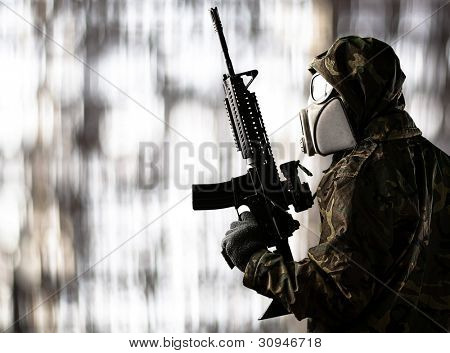 portrait of a soldier wearing a gas mask and aiming with a shot gun against an abstract background