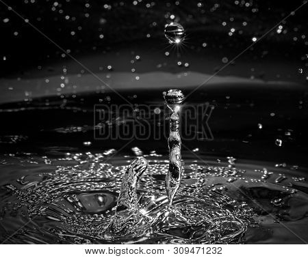 Water Drops Splashing Into Beads To Create Shapes In A Galaxy Of Stars, Monotone Flash Photography