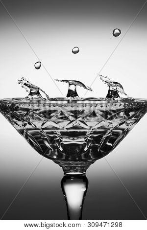 Water Drop Splashes Into A Crystal Glass Collide And Form Three Umbrella Shapes, Monotone Flash Phot