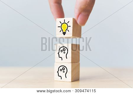 Concept Creative Idea And Innovation. Hand Picked Wooden Cube Block With Head Human Symbol And Light