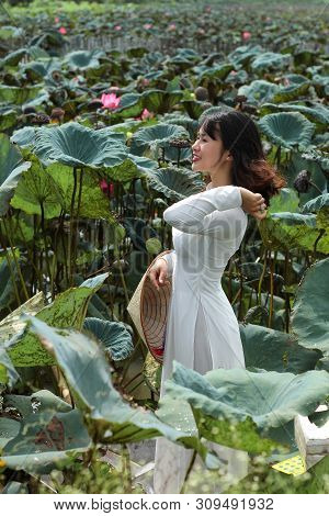 Hanoi, Viet Nam - July 22,2018: Beautiful Woman In White Tradition Long Dress Took A Picture With Pi