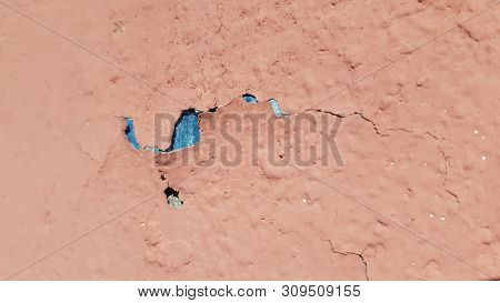 Abstract Background Of Damaged Painted Surface Closeup With Flaking Coral Paint And Blue Paint Under