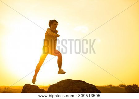 Young Beautiful Woman Runner Jumping from the Rock on the Mountain Trail at Hot Summer Sunset. Sport and Active Lifestyle Concept.