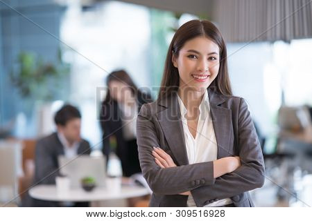Portrait Of Successful Young Asian Businesswoman at Office, Colleagues In Background.