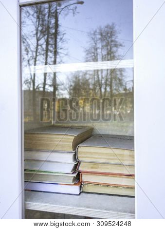 Shelves with books in white wooden cupboard. Library with stacks of books. Knowledge concept. poster
