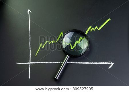 Black Magnifying Glass On Chalk Drawing Green Line Stock Or Company Performance Graph And Chart On B