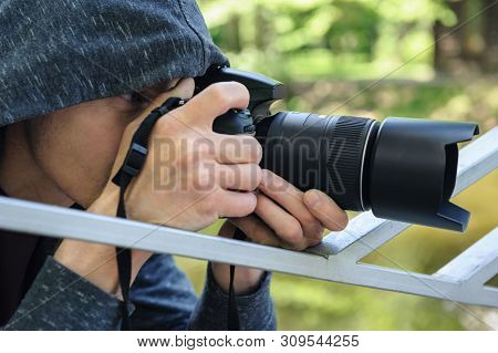 The Photographer Hidden With The Camera. A Man In A Hood Is Taking Pictures Hidden.a Man In A Hood I