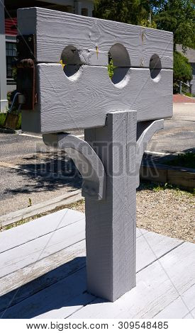 Grey Wooden Post With Pillory Or Stocks Used For Restraint Of A Person For Punishment And Public Hum