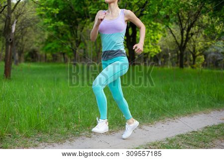 Sports Brunette Girl Jogging In The Park. Green Forest On The Background.