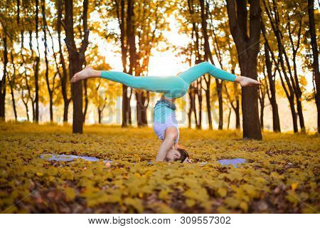 Thin Brunette Girl Plays Sports And Performs Yoga Poses In Autumn Park On A Sunset Background. Woman