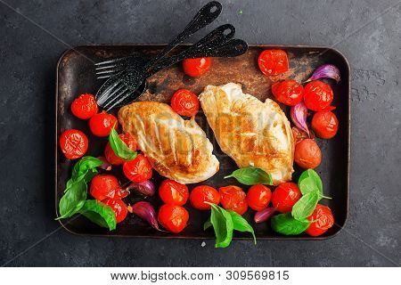 Grilled Chicken Breast Fillet With Young Garlic, Cherry Tomatoes On A Baking Sheet With Basil Leaves