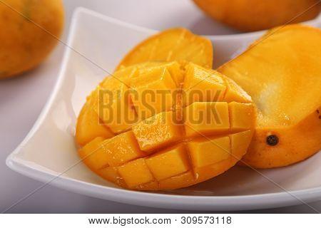 Fresh Organic Mango Fruit Sliced In A White Plate