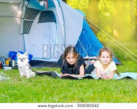 Camp In The Tent - Girls With Little Dog Chihuahua Sitting Together Near The Tent. Camping With Chil
