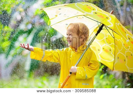Child Playing In The Rain. Kid With Umbrella.