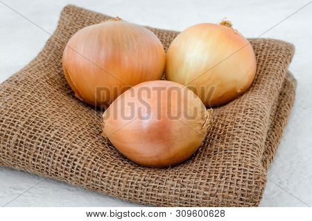 Three Fresh Yellow Onions On A Rough Sackcloth Or Burlap Fabric Over White Coarse Background. Vegeta