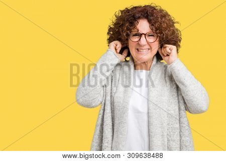 Beautiful middle ager senior woman wearing jacket and glasses over isolated background covering ears with fingers with annoyed expression for the noise of loud music. Deaf concept.