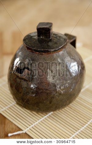 Small, brown, handmade ceramic teapot with lid