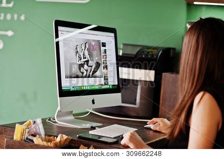 Kyiv, Ukraine - January 20, 2018: Girl Sitting Against Apple Imac In Office And Looking You Tube Mus