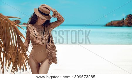 Beautiful Luxury Portrait Of Brunette Woman In Beige Hat, Boho Swimsuit Posing By Ocean Water. Sexy